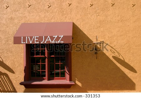 "A ""Live Jazz"" sign over a window at an Italian restaurant. - stock photo"