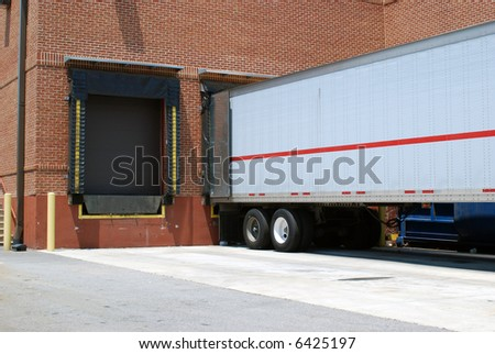 A loading dock with a trailer occupying one of the bays. - stock photo