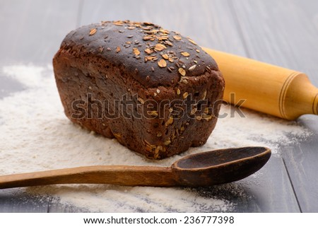a loaf of black bread, rolling pin and wooden spoons on the table - stock photo