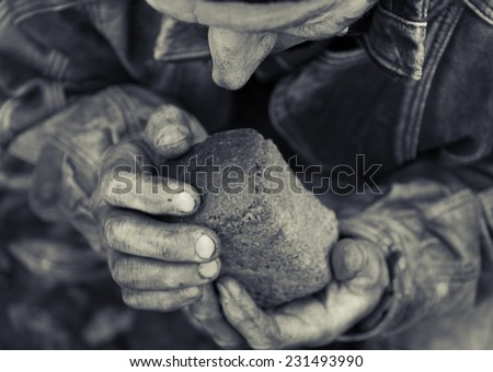 A loaf of bread in an old mans hands - stock photo