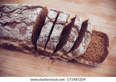 A loaf of fresh rustic wholemeal rye bread, sliced �¢??�¢??on a wooden board, close up. - stock photo