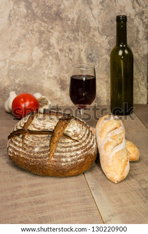 A loaf of fresh rye bread on a table with a wine bottle