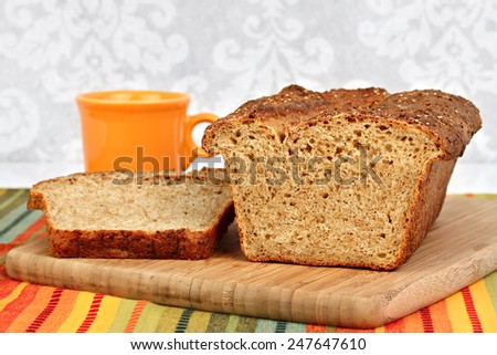 A loaf of freshly baked, homemade quinoa bread on a bread board.  Close up macro view. - stock photo