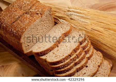 A loaf of wheat bread with a shock of wheat on a wooden cutting board - stock photo