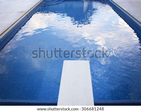 a local public pool without any people in it with a diving board and reflections of clouds  - stock photo