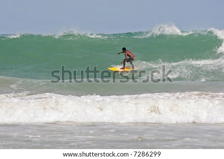 A local surfer tucks into a hollow wave on a beach in Phuket, Thailand - stock photo