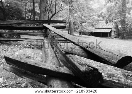 A log cabin in the woods with a split-rail fence in front.  Noah Ogle Cabin, Great Smoky Mountains National Park, near Gatlinburg, TN, USA. - stock photo