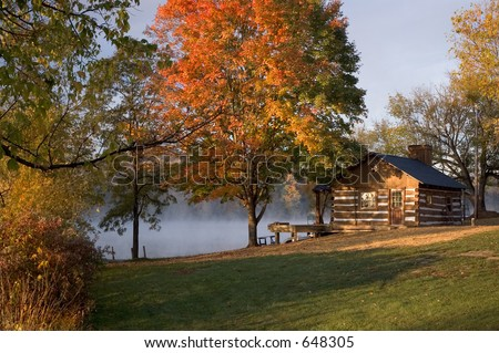 A log cabin on the edge of a lake with early morning mist rising form the lake and fall tree colors.