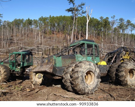 A logging skidder works in a pine forest. - stock photo
