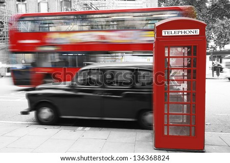 A London taxi stands waiting customers by Telephone Booth, a double decker bus passing in the back ground. Black and White. - stock photo