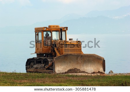 A lone bulldozer with sea in the background  - stock photo