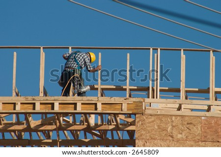 A lone construction worker on top of a new building with a nail gun strapped to his workbelt. No recognizable faces in image. - stock photo