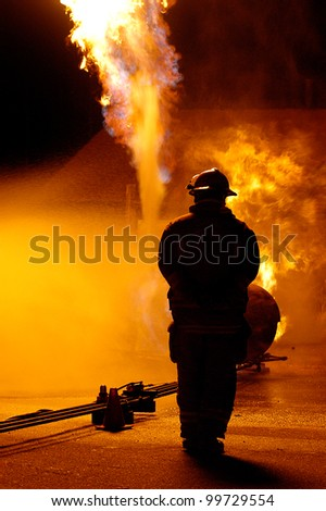 a lone firefighter watcher a blaze. Water is being sprayed to contain the fire - stock photo