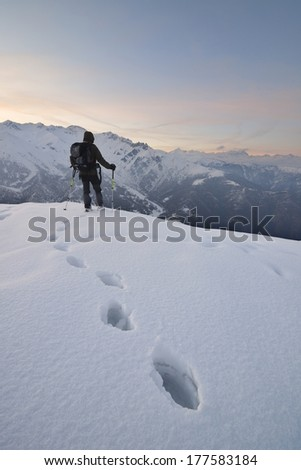 A lone hiker admires the mountains in winter - stock photo