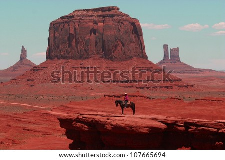 A lone indian rider sits on his horse in front of the famous rock formations of Monument Valley in Arizona, - stock photo