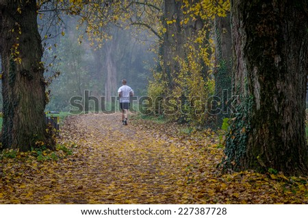 A lone jogger on a trail on a foggy day - stock photo