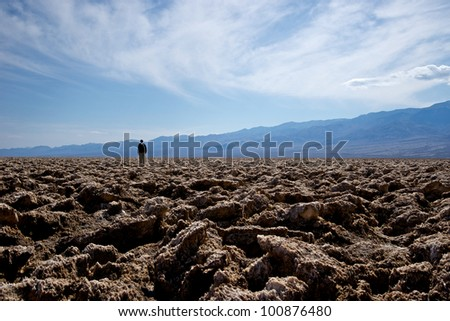 A lone man stands in the distance of the Devil's Golf Course in Death Valley National Park. - stock photo
