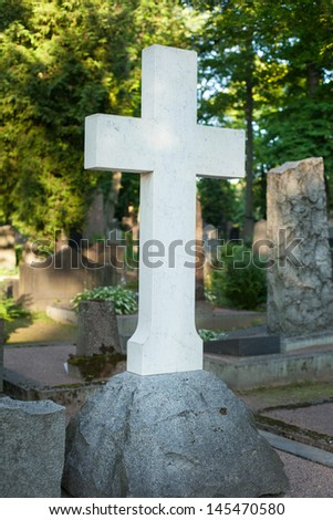 A lone marble cross at a cemetery - stock photo