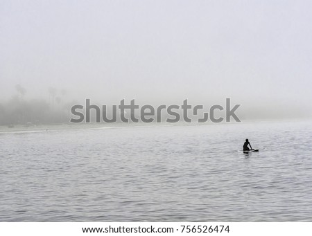 A lone paddle boarder glides through the fog bound waters off of Refugio State Beach near Goleta, CA, USA.