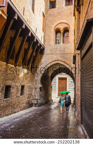 A lone passerby with an umbrella on a narrow street in the old city of Bologna Italy - stock photo
