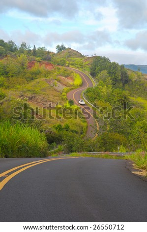 A lone pickup on a curvy, hilly Hawaiian road