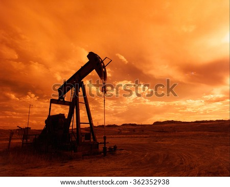 A lone pump jack in an oil field silhouetted against an orange sunset.