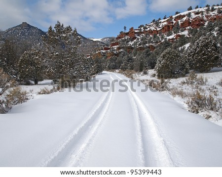 A lone set of tire tracks on a snowy road. - stock photo