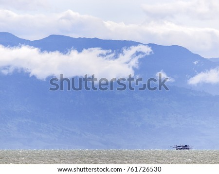 A lone, silhouetted fishing boat glides past the cloudy mountains of Cambodia near Trat, Thailand