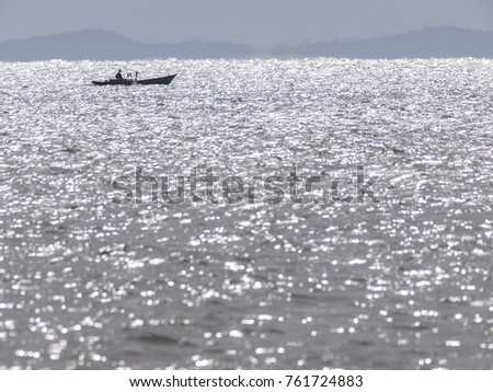 A lone. silhouetted fishing boat out at sea near Ko Chang, Thailand