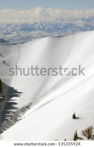 A lone skier descends an extreme slope in the Utah mountains, USA. - stock photo