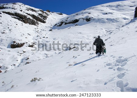 A lone snowboarder begins the hike up a mountain in search of fresh powder in the Maluti Mountains in Lesotho.