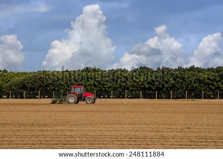 A lone tractor is plowing a field in preparation for seeding - stock photo