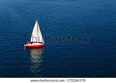 A lone white sail of a red sailboat on a calm blue sea - stock photo