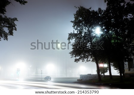 A lonely car drives along empty city street at night after rain. Street is filled with neon light blurred with fog - stock photo