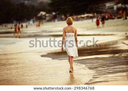 A lonely girl is walking along island coastline and has reflection on wet sand. - stock photo