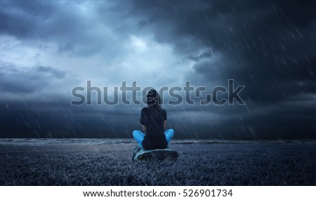 a lonely girl sitting on a wood in a rainy weather.