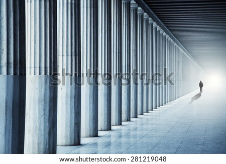 A lonely man walks into the light - stock photo