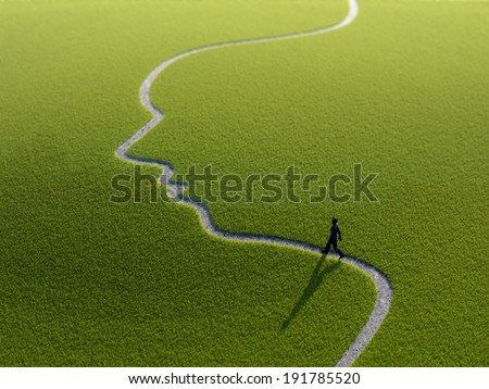 A lonely person walking along a face-shaped path - stock photo