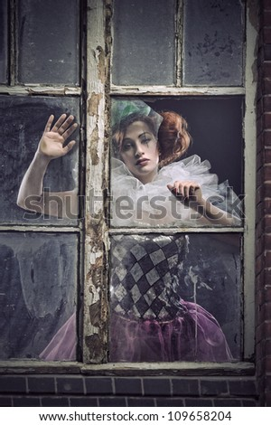A lonely pierrot woman behind the glass - stock photo