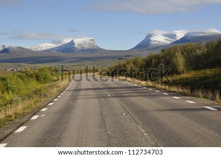 A lonely road leading into a mountain landscape in north of Sweden