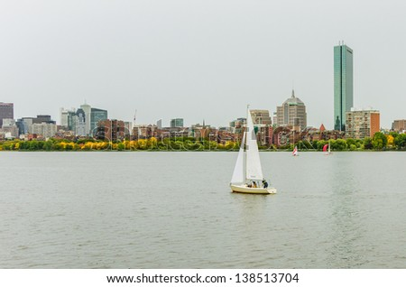 A Lonely Sailing Boat and Boston Skyline on a Rainy Day - stock photo