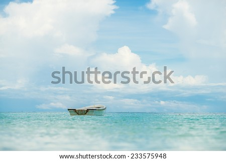 A lonely small boat floating in beautiful tropical ocean, Thailand. - stock photo