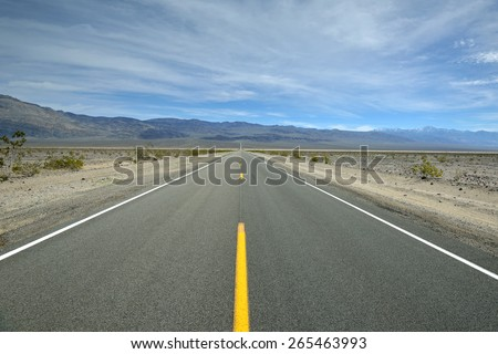 A lonely stretch of road leads through the desert in the Panamint Springs section of Death Valley National Park, California, USA