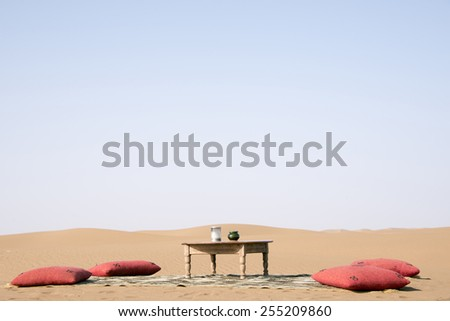 A lonely table on a carpet and four red pillows in the middle of the Sahara desert in Erg Chegaga in Morocco in Morocco in the spring. - stock photo