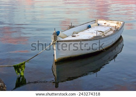 A lonely white boat tied with a rope - stock photo