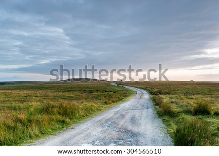 A lonely winding track through desolate moorland on Bodmin Moor in Cornwall - stock photo