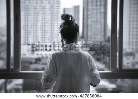 A Lonely woman looking out of window, Sad concept. Missing concept. black and white  tone filter (with selective focus and soft focus effect)