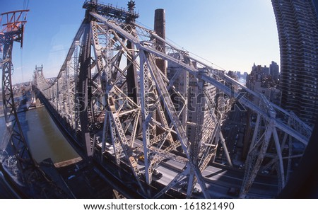 A long bridge crossing the river of a big city. - stock photo