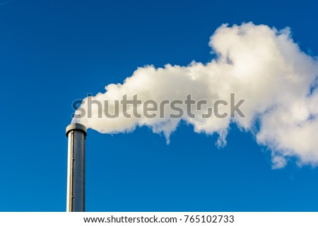A long cloud of white smoke getting out of a metallic chimney against a deep blue sky.