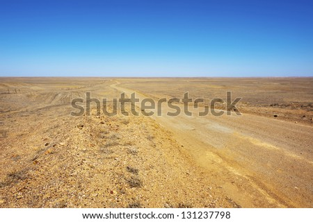 A long dirt road leads further into the arid desert. - stock photo